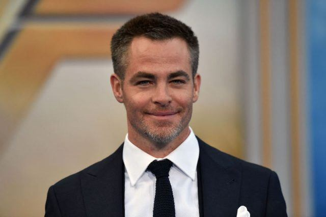 Chris Pine smiling while on a red carpet.
