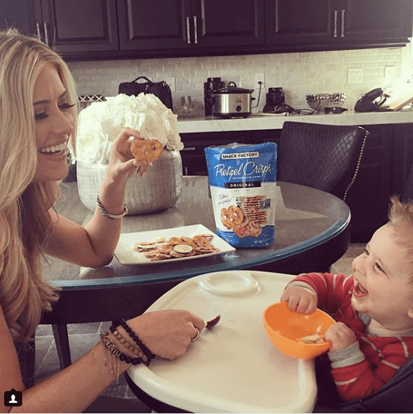 Christina El Moussa eating snacks with her child in her kitchen