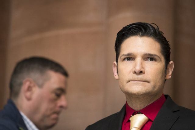 Corey Feldman in a red shirt, yellow tie and black suit.