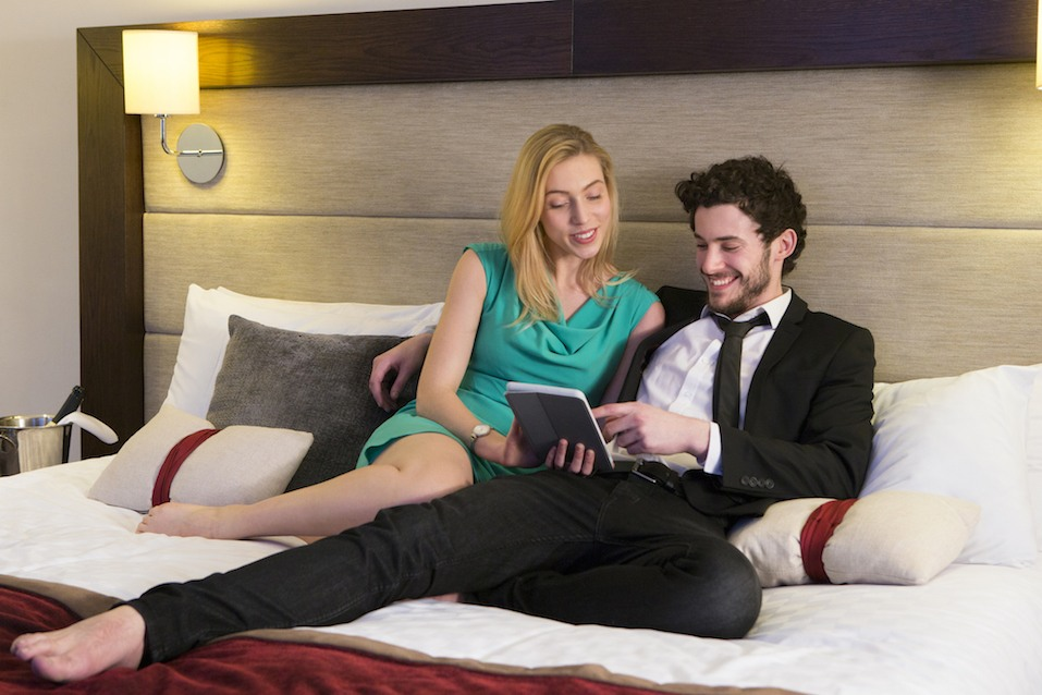 Young couple lying on their bed in their hotel room