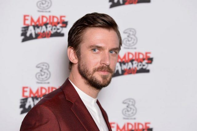 Dan Stevens wears a red blazer while on a red carpet.