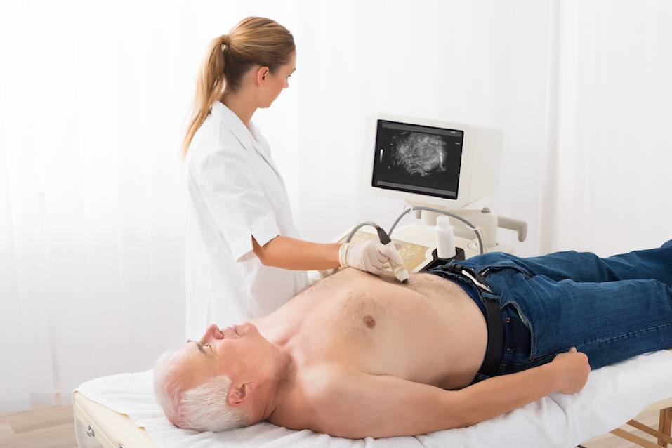 Doctor Using Ultrasound Scan On Abdomen Of Senior Male Patient
