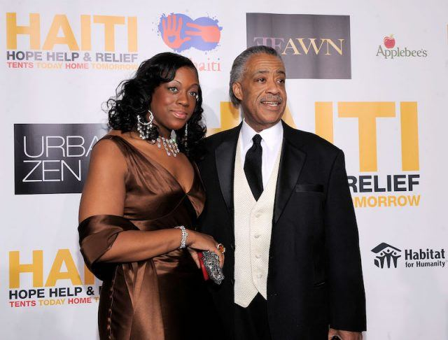 Dominique Sharpton posing on a red carpet with her father.