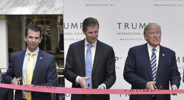 Donald Trump Jr, Erice Trump and Donald Trump standing in front of a red tape.