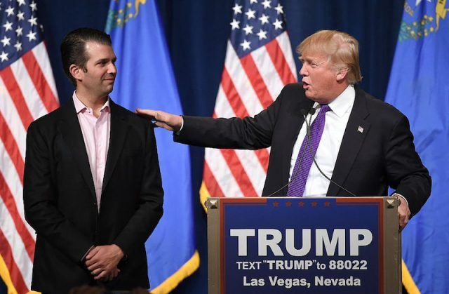 Donald Trump Jr. stands next to his father, Donald Trump while he speaks at a podium.