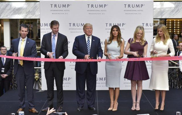 The Trump family lined behind a tape at a grand opening event.