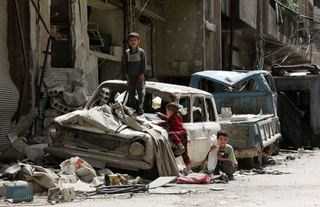 Syrian boys play on a destroyed car in the former rebel-held Syrian town of Douma