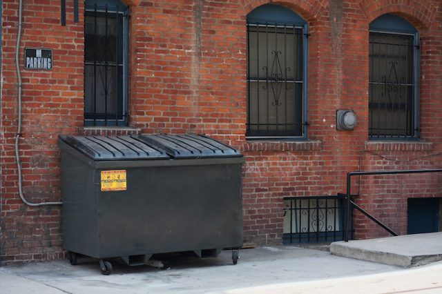 A dumpster in front of a building.