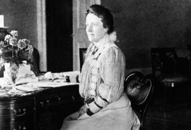 Edith Roosevelt sitting at a desk decorated with flowers.