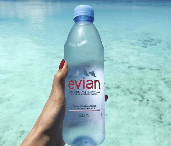 A woman holds a bottle of Evian.