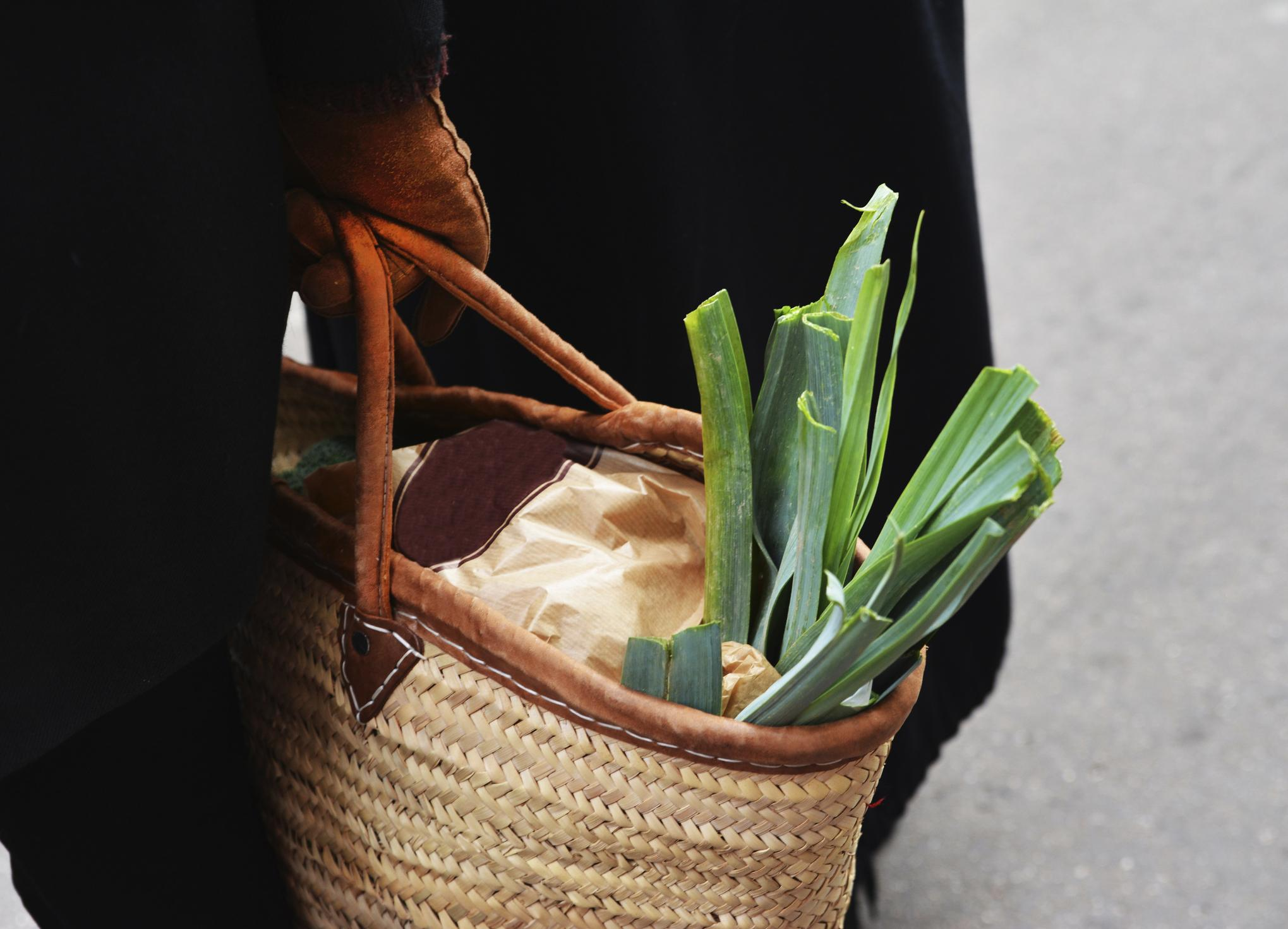 leek in a straw reusable grocery bag farmers market