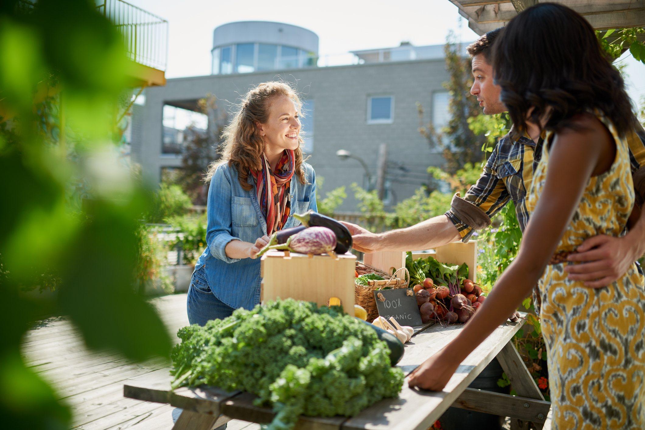 Friendly woman tending an organic vegetable stall at a farmer