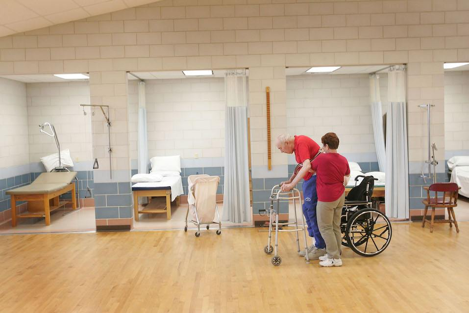A physical therapy aid helping a man in a nursing home