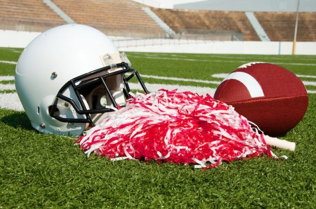 A football helmet, football and pom poms on a green field.