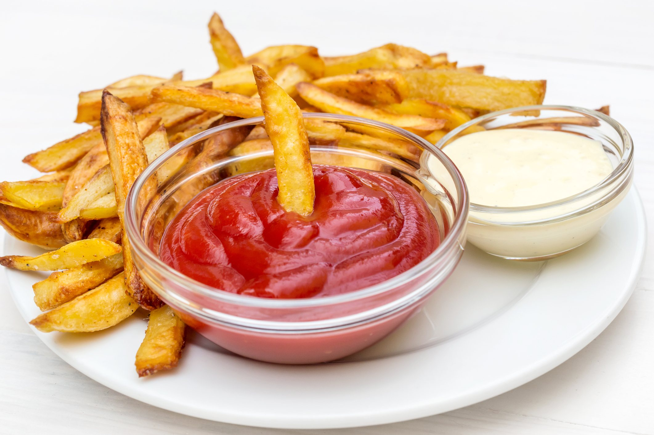 Plate with fries potato, ketchup and mayonnaise on the table.