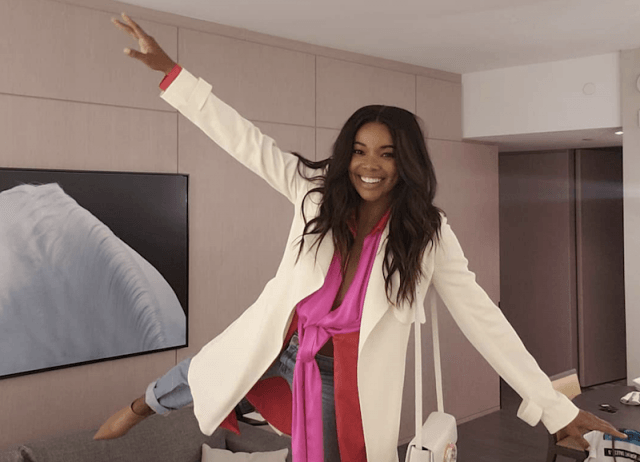 Gabrielle Union smiling and posing in her hotel room.