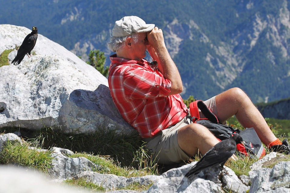 A elder male tourist looks out with field glasses