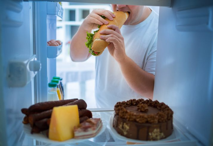 man eating out of refrigerator