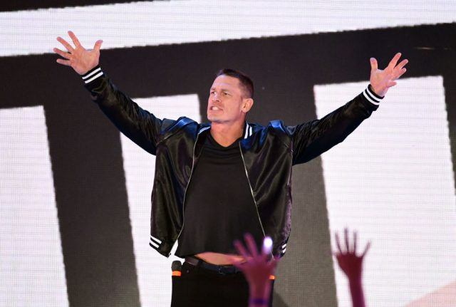 John Cena cheering on with a crowd while on stage.
