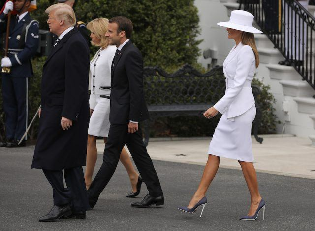 Melania Trump walking behind in high heels and white outfit and hat.