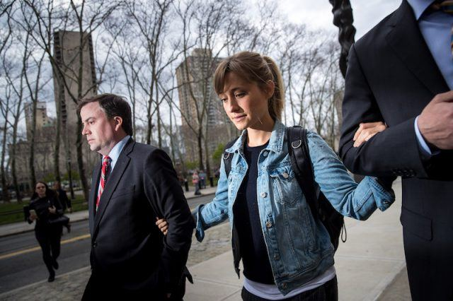 Allison Mack walking into a courtroom with her lawyers and representation.