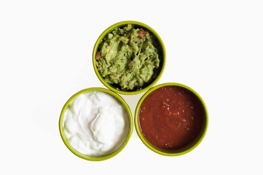 Three bowls filled with salsa guacamole and sour cream, close-up
