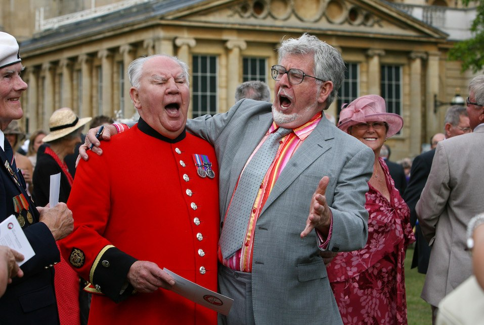 Rolf Harris sings a song with Chelsea pensioner David Poultney at a Buckingham Palace garden party