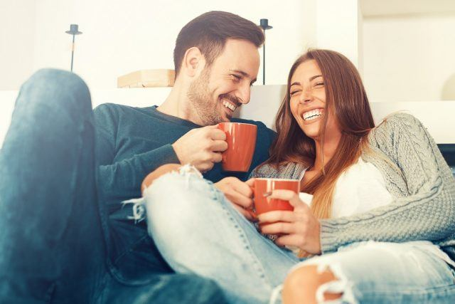 Happy couple sitting on a couch drinking from mugs.