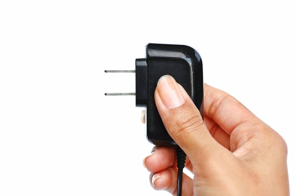 Hand holding Electric plug