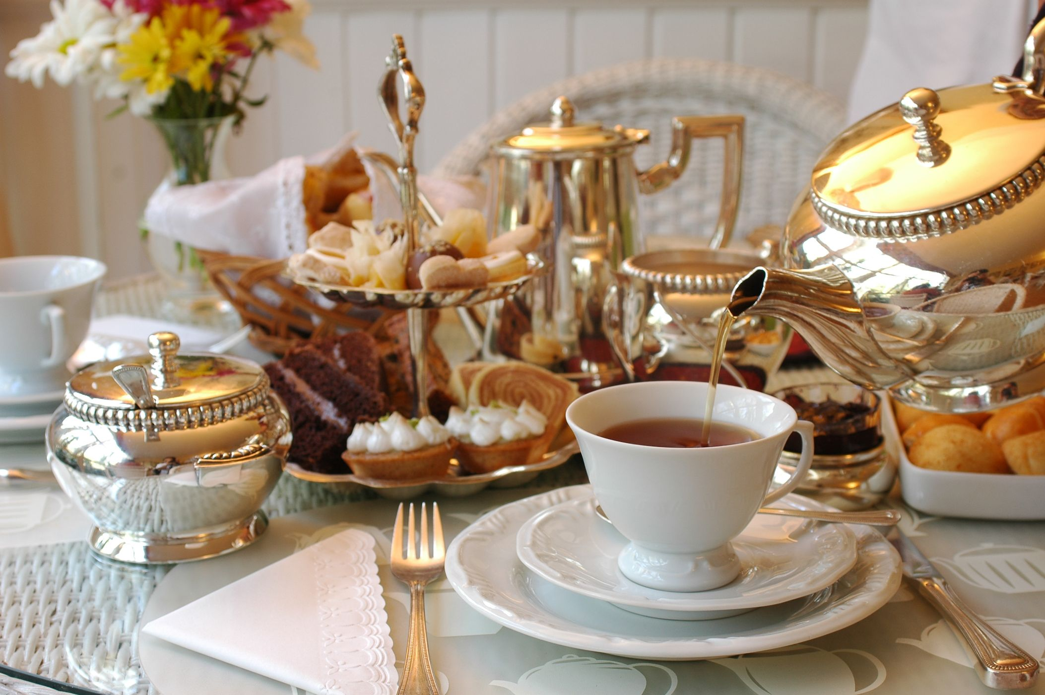 Tea being poured into a cup on a table set for afternoon tea