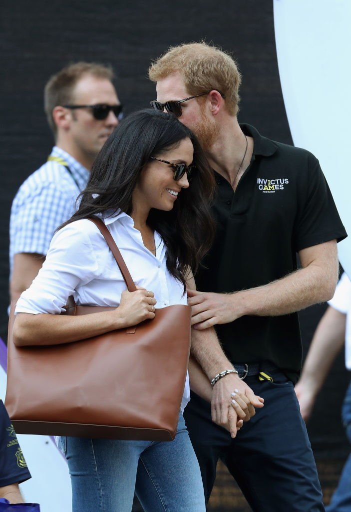 Prince Harry and Meghan Markle hold hands a Wheelchair Tennis match during the Invictus Games 2017