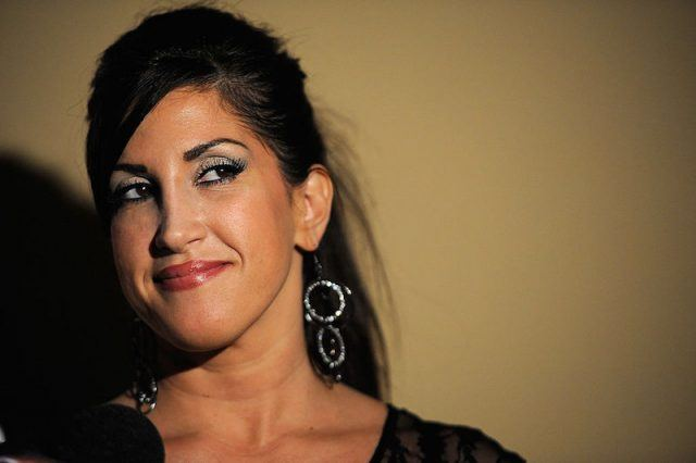 Jacqueline Laurita smiling while posing against a wall.