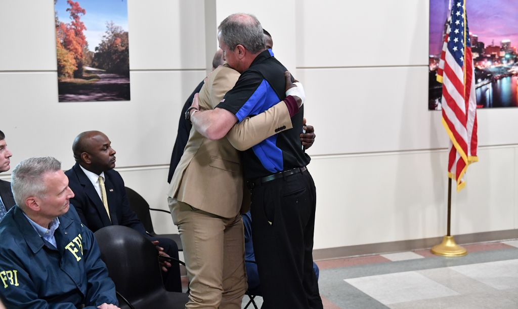Waffle House President and CEO, Walt Ehmer embraces patron James Shaw Jr. at a press conference.