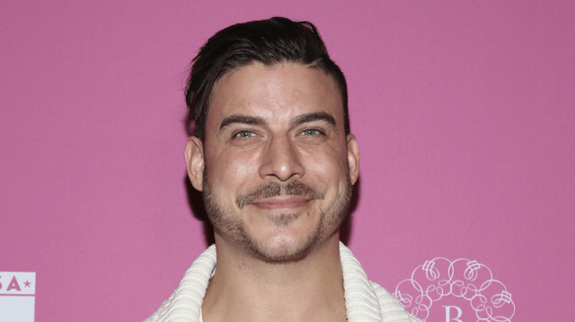 Taylor smiles and poses on a red carpet, in front of a pink backdrop.