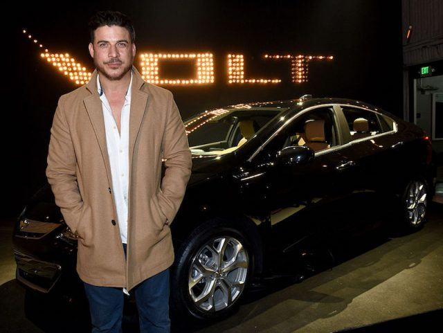 Taylor posing in front of a shiny, black car.