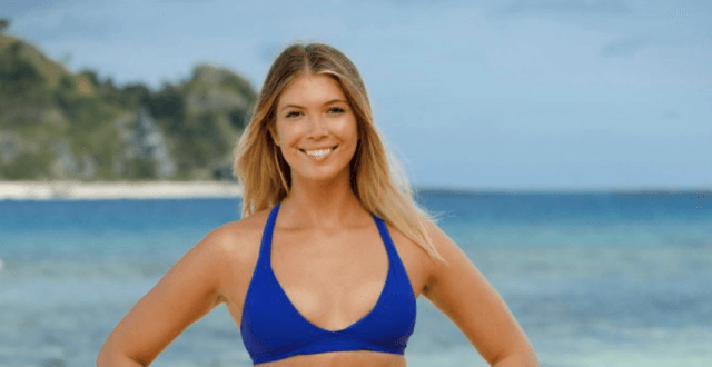Jenna Bowman smiles while posing in front of a beach on the island.