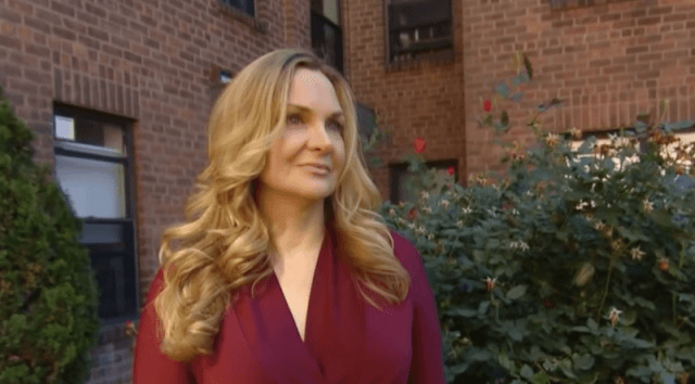 Jill Harth stands in front of a brown brick building.