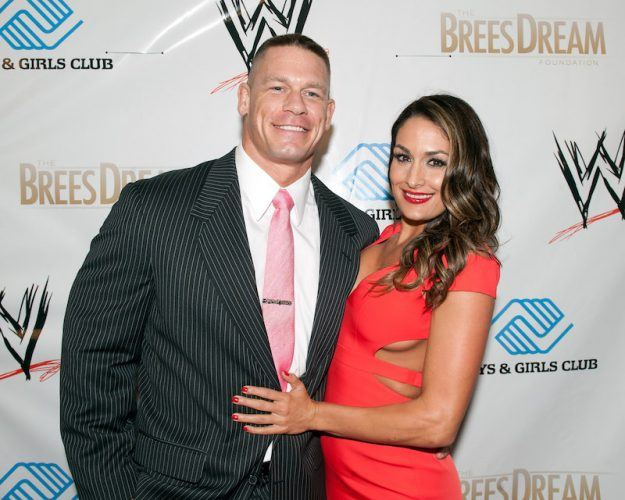 John Cena and Nikki Bella posing on a red carpet.