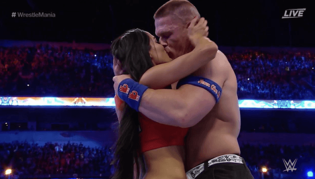 John Cena and Nikki Bella embracing in the ring after their proposal.