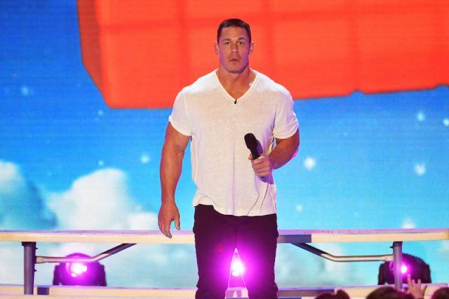 John Cena on stage, holding a microphone.