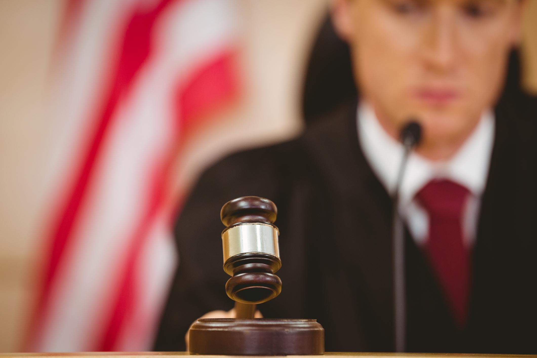Stern judge about to bang gavel on sounding block in the court room
