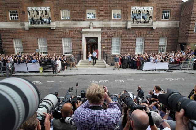 Kate Middleton and Prince William stand in front of the Lindo Wing while the paparazzi gather across the street.