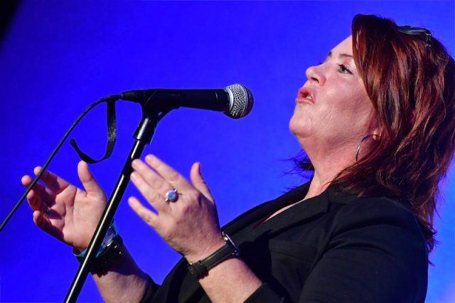 Kathleen Madigan performing in front of a microphone.