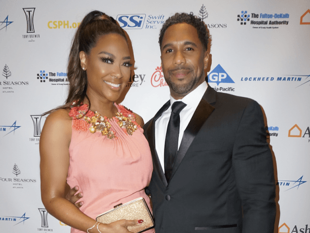 Kenya Moore smiling while next to her husband, Marc.