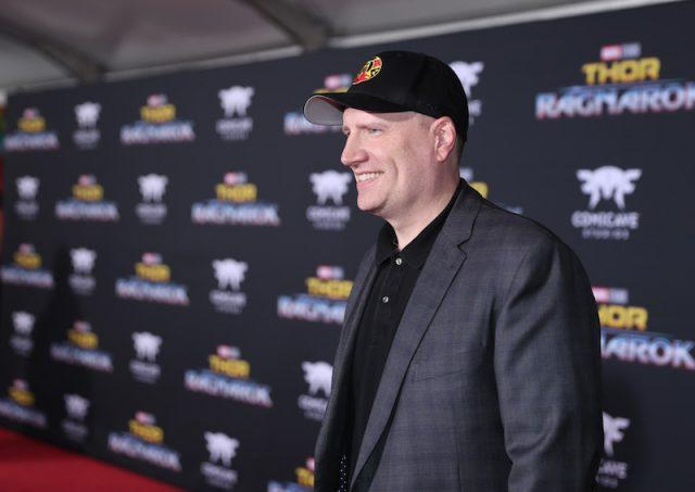 Kevin Feige smiling and posing on a red carpet.