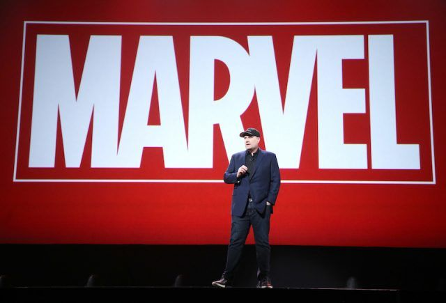 Kevin Feige in front of a large Marvel logo.