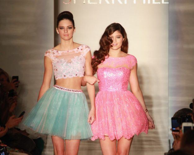 Kendall Jenner and Kylie Jenner walking down a fashion runway.