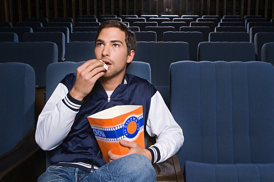 Man eating popcorn and watching movie in cinema