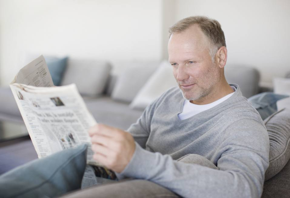 Man sitting on sofa reading newspaper