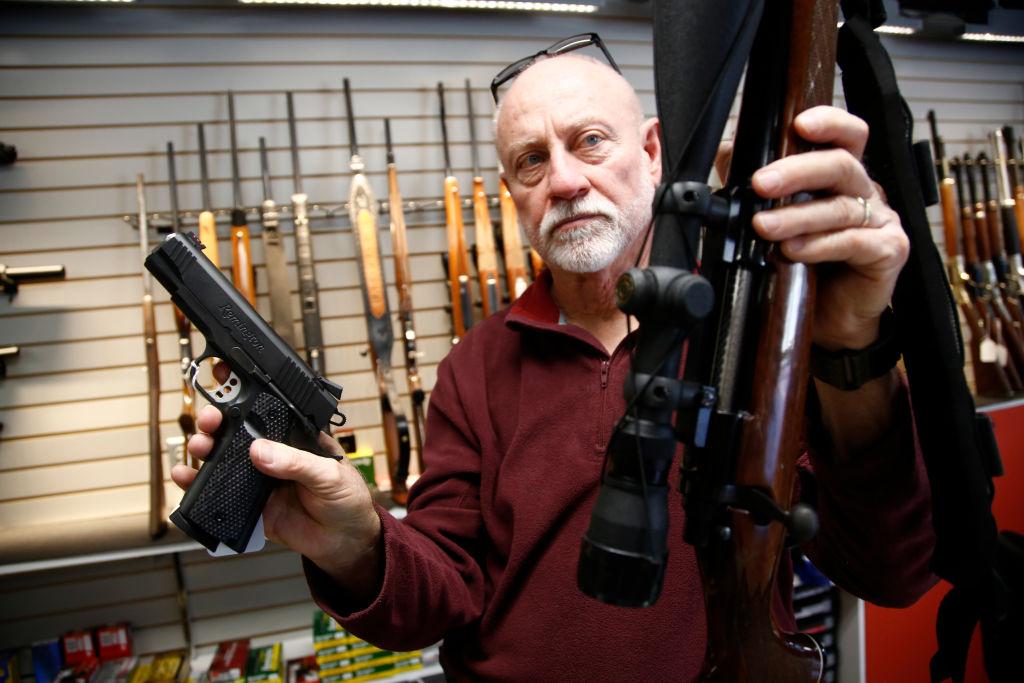 Bret Reid shows off a Remington 700 hunting rifle and a Remington R1 Enhanced model 1911 pistol